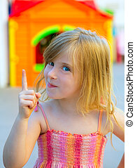 Blond kid girl funny gesture finger up in playground