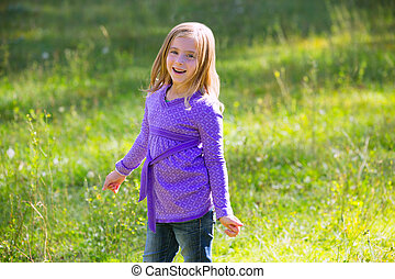 Blond kid girl happy in outdoor green meadow