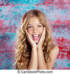 Blond kid girl happy smiling expression hands in face