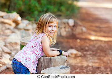 blond kid girl in tree trunk forest