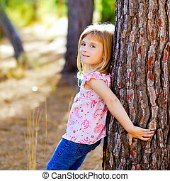 blond kid girl on autumn tree trunk in forest park