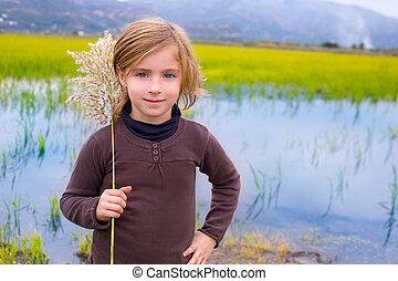 Blond kid girl outdoor holding spike in wetlands lake