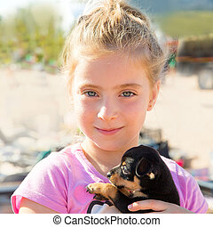 Blond kid girl playing with puppy dog smiling