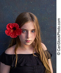 Blond kid girl portrait with red flower in hair