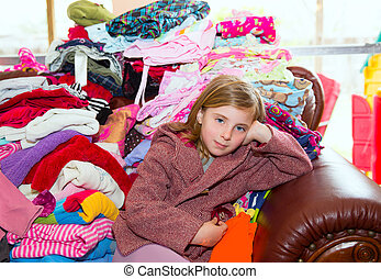Blond kid girl sitting on a messy clothes sofa before...