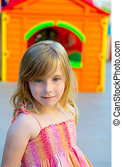Blond kid girl smiling in outdoor playground
