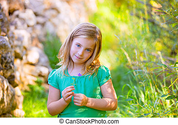 Blond kid girl smiling with purple flower relaxed outdoor