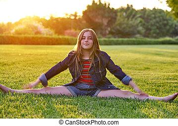Blond kid girl splitting legs at sunset park