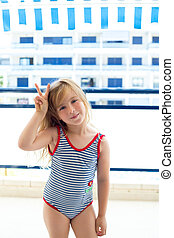 Blond kid girl swimsuit with hands victory sign