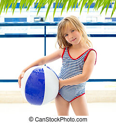 Blond kid girl with swimsuit with summer blue ball