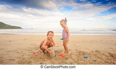 Blond Kids Small Girl Boy Gambol Make Sand Cake on Beach