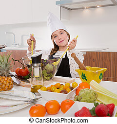 Blond kind girl junior chef on countertop salad - Blond kind...