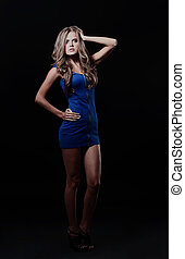 blond lady in blue dress isolated on black.