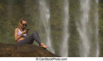 Blond Lady Sits Barefoot on Rock Listens to Music - blonde...