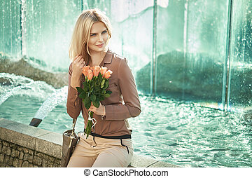Blond lady sitting next to the fountain