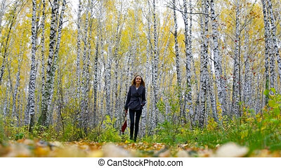 blond lady with red handbag walks among golden birches -...
