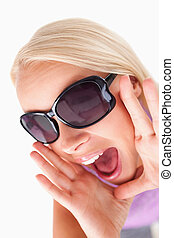 Blond lady with sunglasses in high spirits in a studio