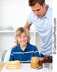 Blond little boy and his father preparing breakfast