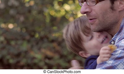 Blond little boy hugging Father