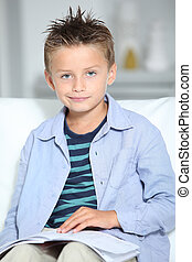 Blond little boy sitting on sofa with book