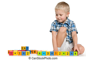 Blond little boy with blocks on the floor