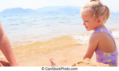 Blond Little Girl Builds Sand Castle on Beach of Azure Sea