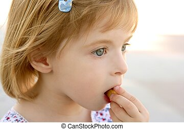 Blond little girl closeup portrait eating biscuit
