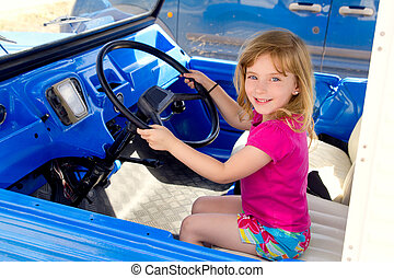 blond little girl driving in convertible