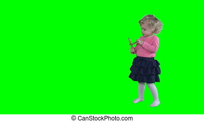 Blond little girl playing with wooden rattle toy isolated on green background