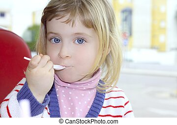 blond little girl portrait eating with spoon