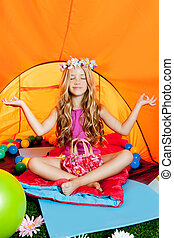 Blond little girl practicing yoga in orange camping tent