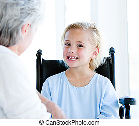 Blond little girl sitting on a wheelchair talking with her...