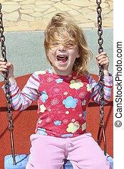 blond little girl swinging in park swing messy hair