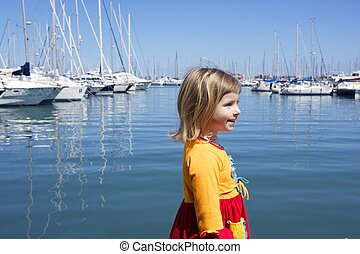 blond little girl waling in blue marina