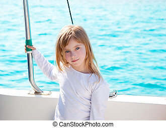 blond little kid girl sailing in a boat smiling
