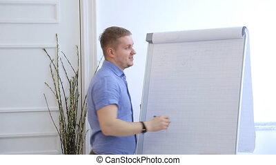 Blond man in blue shirt draws schemes on flipchart with white paper