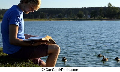 Blond man looks at photos. Ducks swim nearby in a lake