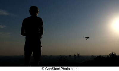Blond man operates a drone with a control panel at sunset in slo-mo