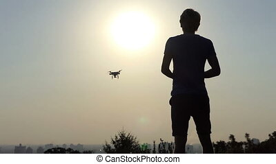 Blond man operates his flying drone with panel at sunset in slo-mo