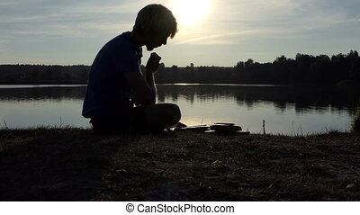 Blond man reads a book on a lake bank at sunset in slo-mo