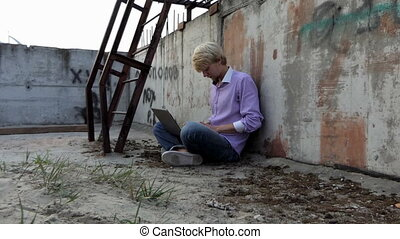 Blond man sits on a construction site and works at his laptop