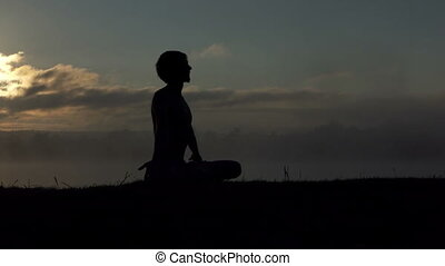 Blond man sits on a lake bank and practices yoga at sunset in slow motion