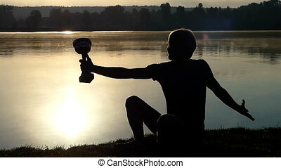 Blond man sits on a lake bank looking at a winner bowl in slo-mo
