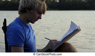 Blond Man Sits, Reads And Writes His Notes on a Riverbank at Sunset in Slo-Mo