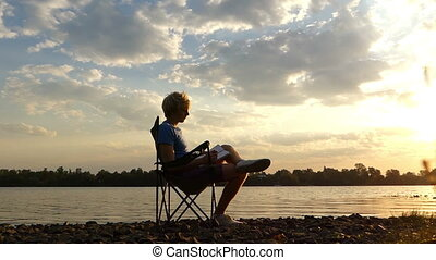 Blond Man Sits, Reads, Stretches Out on a Riverbank at Sunset in Slo-Mo