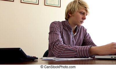 Blond Man Writes a Document, Looks at a Laptop, Sitting at a Table in an Office