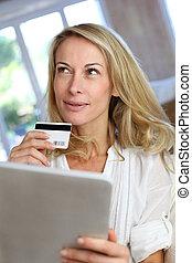 Blond mature woman doing online shopping