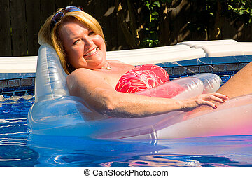 Blond mature woman relaxing pool
