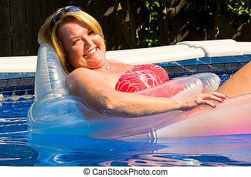 Blond mature woman relaxing pool - Blond mature woman...