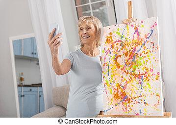 Blond mature woman taking selfie